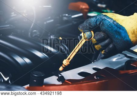 Mechanic Hand Pulling Up Oil Dipstick Of The Car Engine For Checking Oil Level