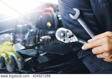 Car Mechanic Holding Wrench In The Auto Repair Garage