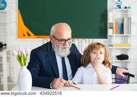 Teacher And School Boy Doing Homework Assignment At School.