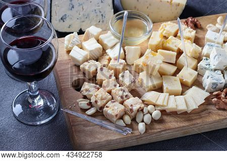 Elite Cheeses: With Truffle, Dor Blue, Brie, Parmesan And Assortment Of Nuts On A Wooden Board On Gr