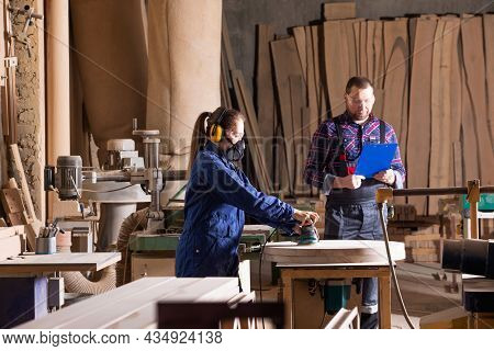 Young Female Apprentice Polishing Wood Under Senior Colleague Supervision