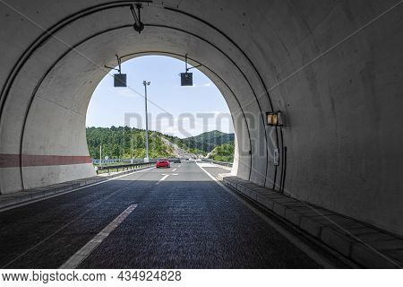 Concrete Tunnel With Asphalt Road On The Highway.