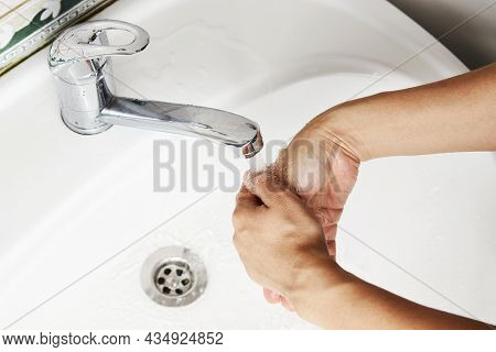Woman washing hands with the water tap. Washing hands with soap, close-up. Coronavirus prevention, h