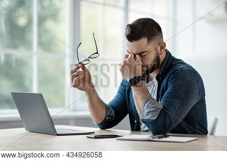 Frustrated Young Man In Shirt, With Laptop At Remote Job, Takes Off Glasses, Rubs Eyes