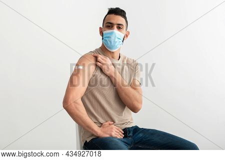 Vaccinated Arab Man In Face Mask Showing Arm With Band Aid After Covid-19 Vaccine Shot On White Stud