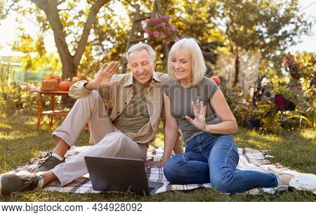 Online Communication. Modern Senior Spouses Using Laptop And Video Calling Family, Sitting On Picnic