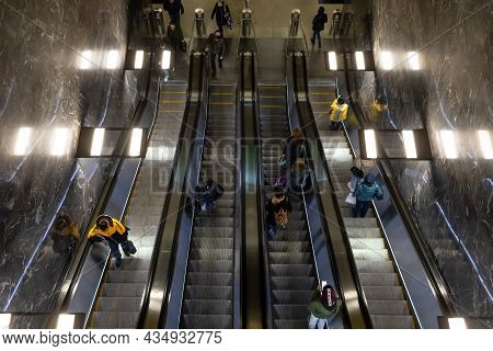 Moscow, Russia - October 2021: People On Escalators In Metro Station, Top View. Passengers Crowd On