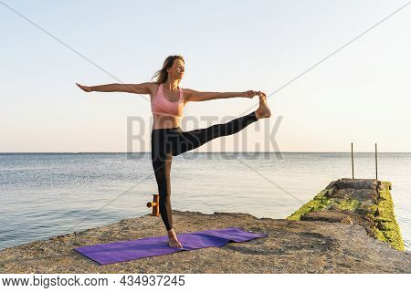A Woman Practicing Yoga, Standing On A Mat On The Pier, Performs The Exercise Uttita Hasta Padangush