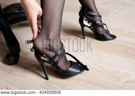 Tired Female Legs, Foot Pain, Woman In Black Stockings With Removed Black Shoes On High Heels Sittin