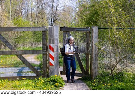 Female Tourist Passing A Fence With Her Mobile Phone Gimbal Tripod Head Stabilizer In Hand, Oostvaar