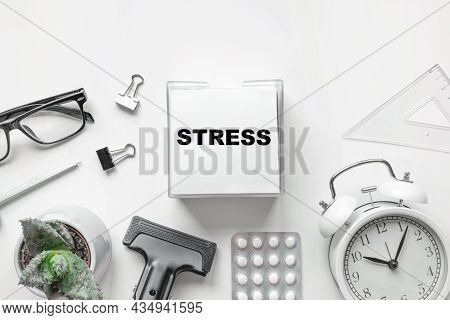 Blank Of Notepad With The Word Stress, Pen, Clock And Antidepressants On White Background. Top View,