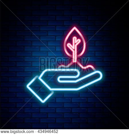 Glowing Neon Line Plant In Hand Of Environmental Protection Icon Isolated On Brick Wall Background.