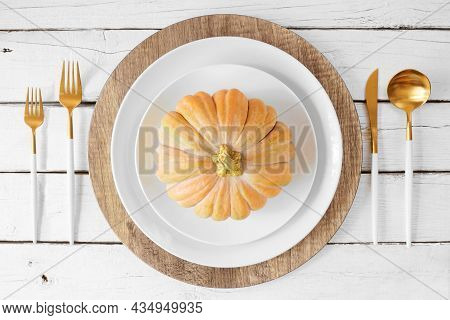 Autumn Harvest Or Thanksgiving Dinner Table Setting With Plates, Flatware And Frosty Pumpkin Decor.