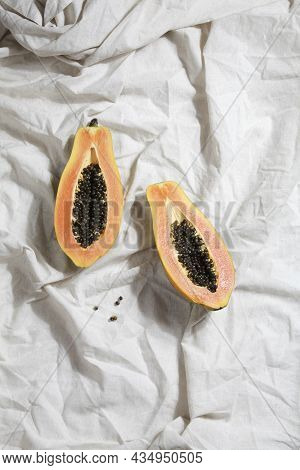 Creative Food Concept With Half Papaya On Crumpled Gray Linen. Flat Lay Top View. Minimalist Colorfu