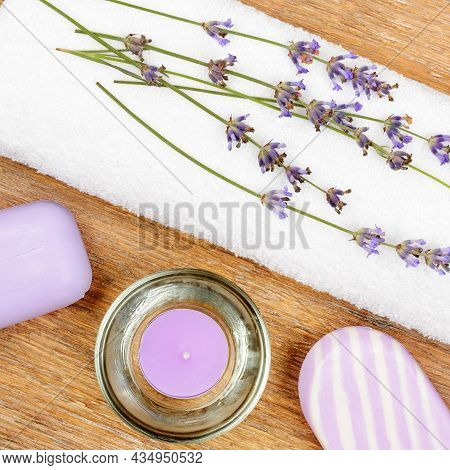 Spa Accessories: Lavender Soap, Scented Candle, Dried Lavender Flowers And A Towel On A Wooden Backg