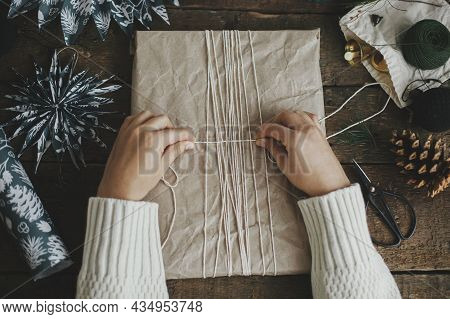 Hands Wrapping Stylish Christmas Gift In Craft Paper With String On Rustic Wooden Table With Blue Pa