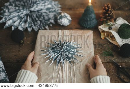 Wrapping Christmas Gift, Atmospheric Image. Hands Decorating Stylish Xmas Gift In Craft Paper With B
