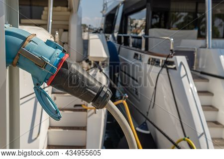 Close-up Of A Power Station With A Luxury Yacht Receiving Power Through A Cable Plugged Into Electri