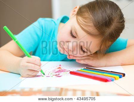 Cute cheerful child drawing using felt-tip pen while sitting at table