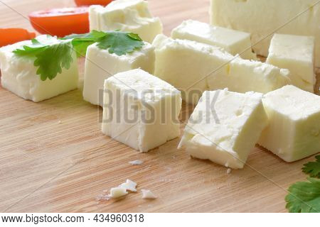 Feta Cheese With Cherry Tomatoes And Coriander On A Bamboo Chopping Board.  The Most Famous Greek Ch