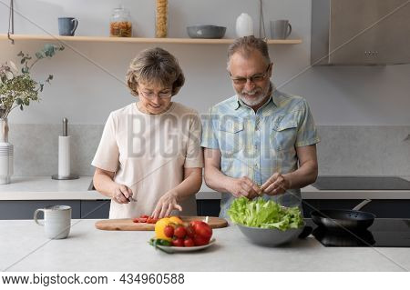 Happy Bonding Middle Aged Couple Cooking At Home.