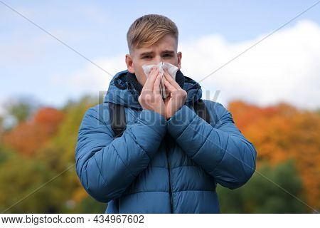 Handsome Guy Blowing His Nose In A Paper Handkerchief Outdoors On Natural, Golden Autumn Background.