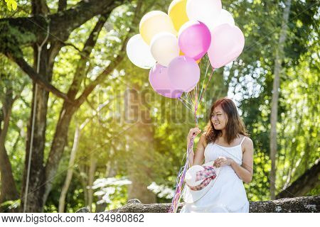 Cheerful Beauty Woman Holding Balloons Relax Sitting Under Big Tree In Green Park With Happiness. Wo