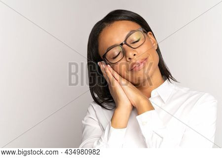 Relaxed African Businesswoman Lying On Folded Hands With Eyes Closed. Exhausted Tired At Work Female