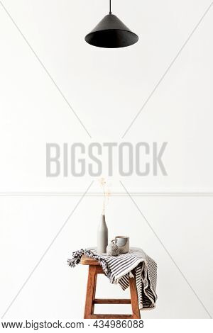 Vase of gypsophila flower on a wooden stool in a white room