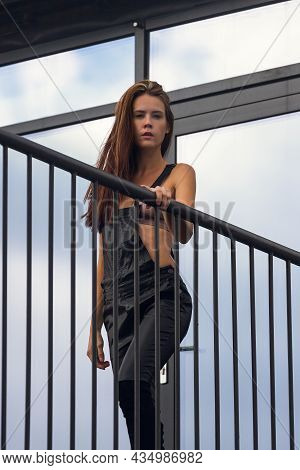 Outdoor Close-up Portrait Of A Young Beautiful Woman In A Leather Overalls And Top Posing Against  W