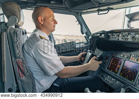 Confident Pilot Sitting In The Cockpit And Holding The Steering Wheel