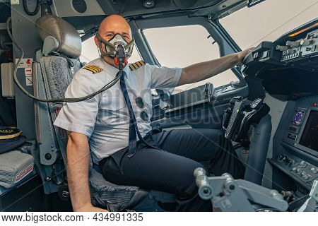 Adult Male Pilot Wear Air Mask In Cockpit Of Airplane