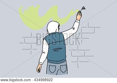 Street Art And Graffiti Concept. Young Man Standing Backwards Making Graffiti With Yellow Color On W