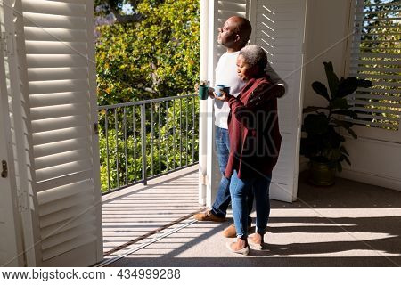 Relaxed african american senior couple drinking coffee standing on balcony in sun. retirement lifestyle, spending time at home and garden.