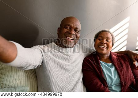 Happy african american senior couple taking selfie at home. retirement lifestyle, communication technology and spending time at home.