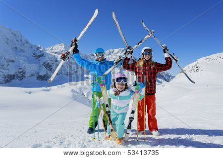 Ski, skiers, sun and fun - family enjoying winter vacation