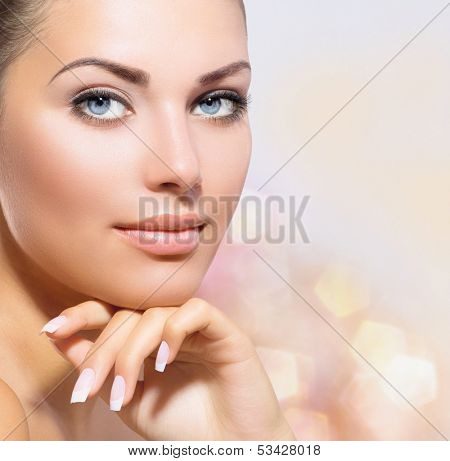 Beauty Portrait. Beautiful Spa Woman Touching her Face. Perfect Fresh Skin closeup. Over Pink Blurred Background. Pure Beauty Model. Youth and Skin Care Concept