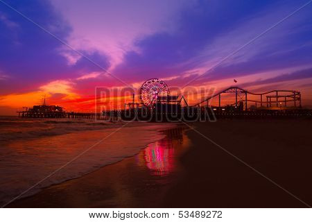 Santa Monica California sunset on Pier Ferris wheel and reflection on beach wet sand