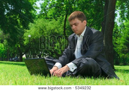 Young Businessman Resting In A Park On The Grass