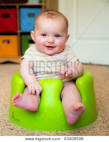 Baby boy using training Bumbo seat to sit up