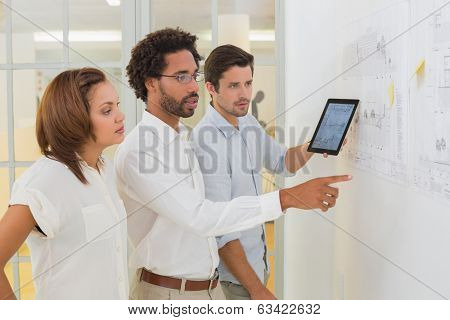 Concentrated business people using digital tablet in meeting at the office