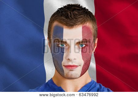 Composite image of serious young france fan with facepaint against digitally generated france national flag