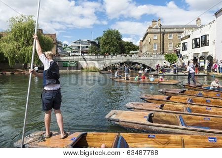 CAMBRIDGE, UK - AUGUST 18: Professional punter in Silver Street with busy River Cam full of tourists in gondolas in background. August 18, 2013 in Cambridge.