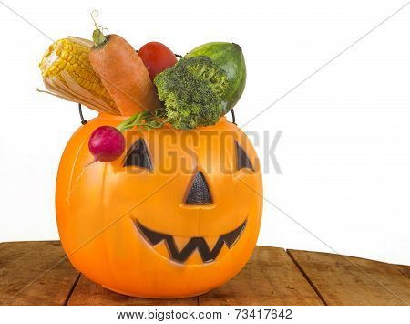 Halloween Healthy plastic Pumpkin full of Vegetables on wooden table on white background