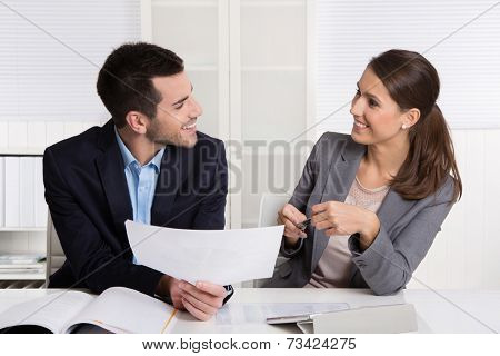 Successful young consultants working as business team in an office analyzing documents.