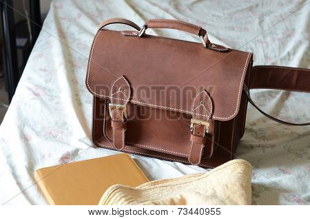 Brown Vintage leather briefcase with strap and brass buckle in vintage bedroom poster