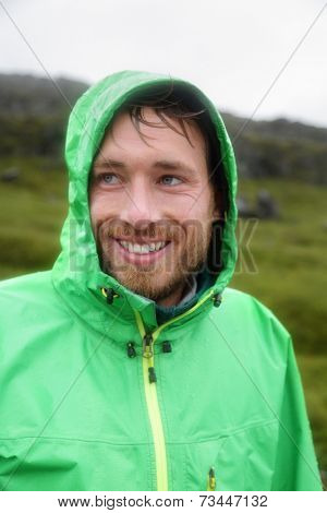 Rain jacket - man smiling outdoors on rainy day. Portrait of male model wearing green rain jackets outside living outdoor lifestyle.