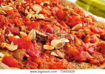 closeup of a coc de tomata, a pie with tomato and tuna typical of Valencia, Spain