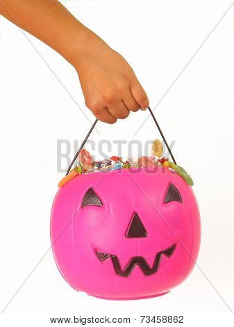 Kid holding a pink plastic pumpkin filled with candy