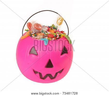 Pink plastic pumpkin filled with candy